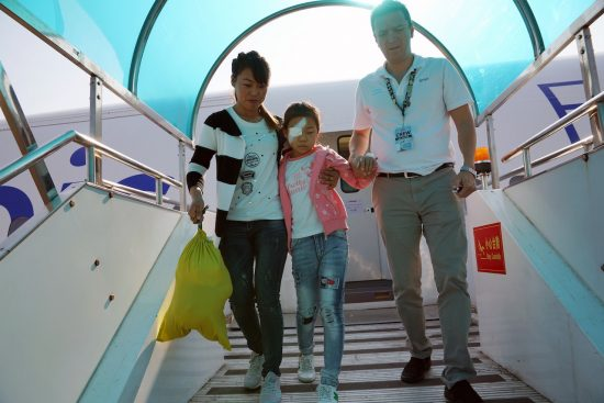 Xiu Ling descending the FlyingEye Hospital with her mother and Orbis staff member